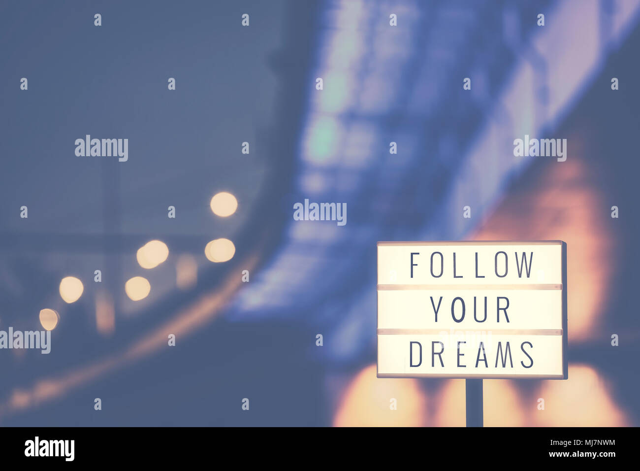 Follow Your Dreams inspirational life quote text in lightbox, city lights in background, color toned picture. - Stock Image