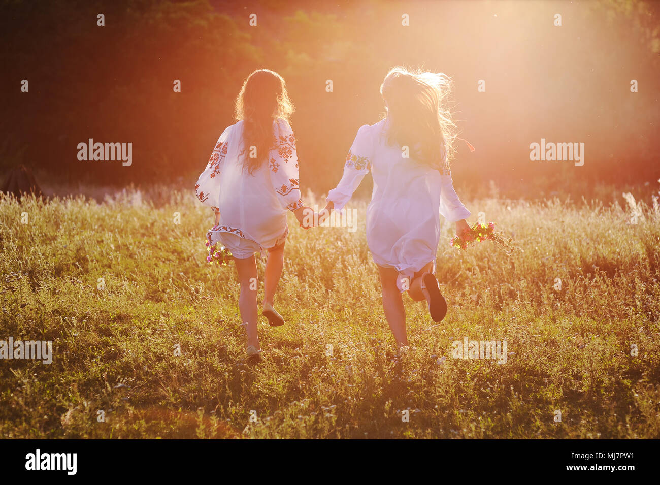 two young beautiful girls in white shirts with floral ornament with flower wreaths in their hands run against the background of nature and grass in the contour or the back light of the sun. - Stock Image