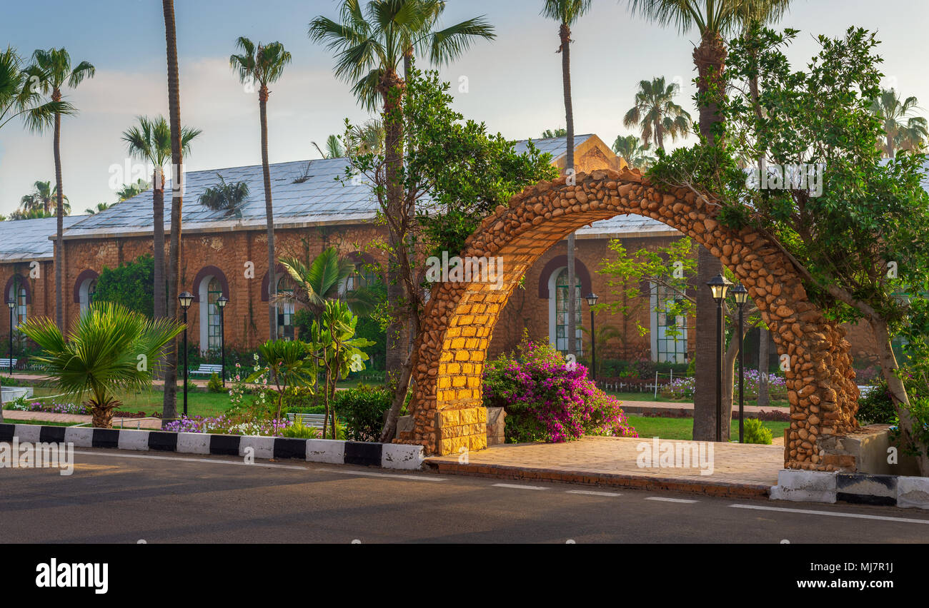 Stone bricks orange arch revealing the royal plant nursery at Montazah public park with trees and palms in sunrise time, Alexandria, Egypt - Stock Image