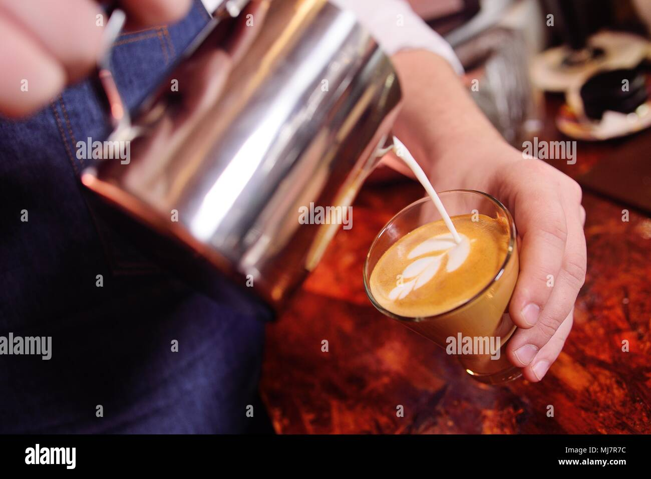 coffee barman prepares coffee with a pattern on the foam or latte-art - Stock Image