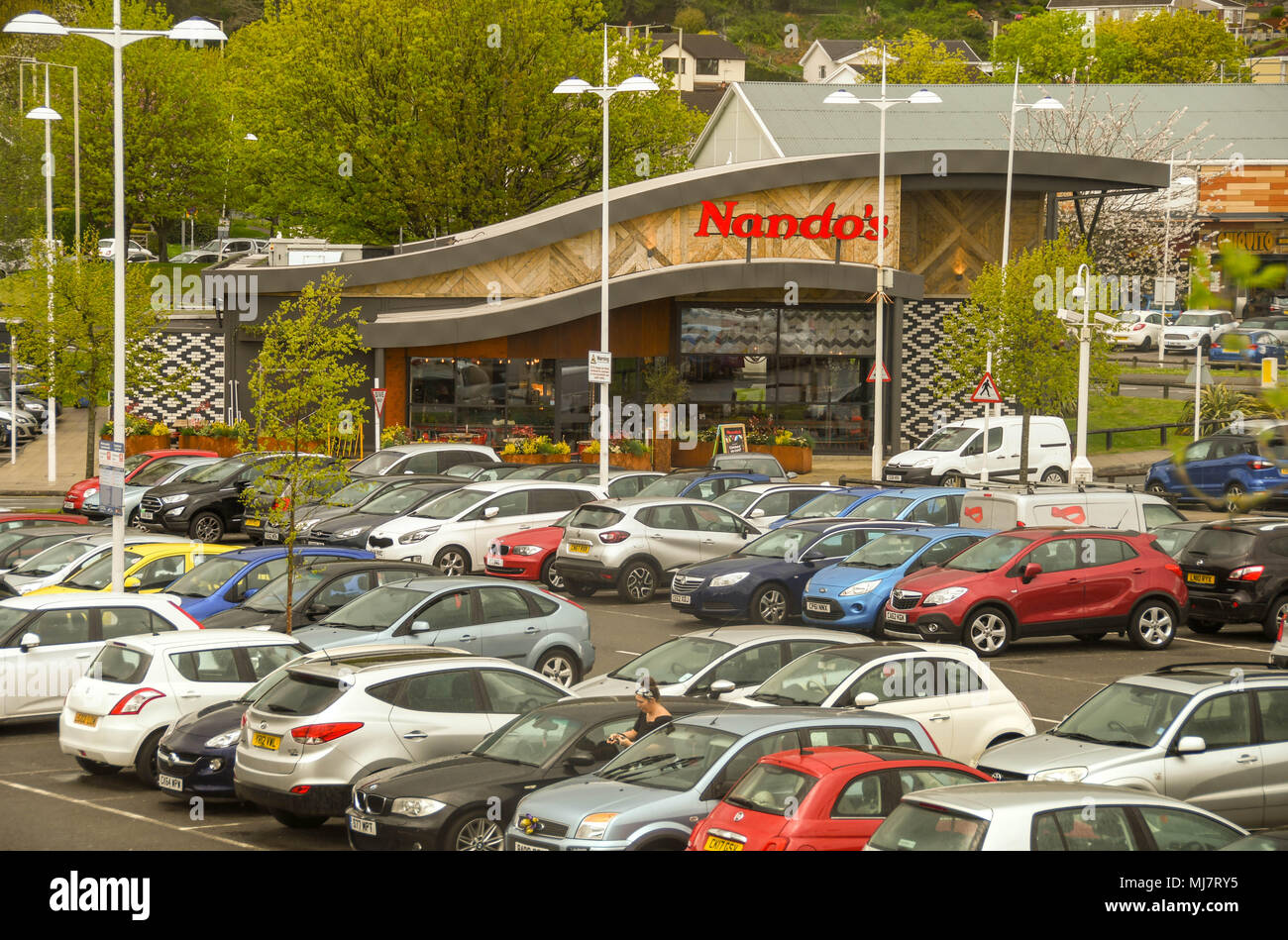 Branch of the Nando's chicken restaurant chain in Talbot Green Shopping Park with cars parked in the foreground - Stock Image