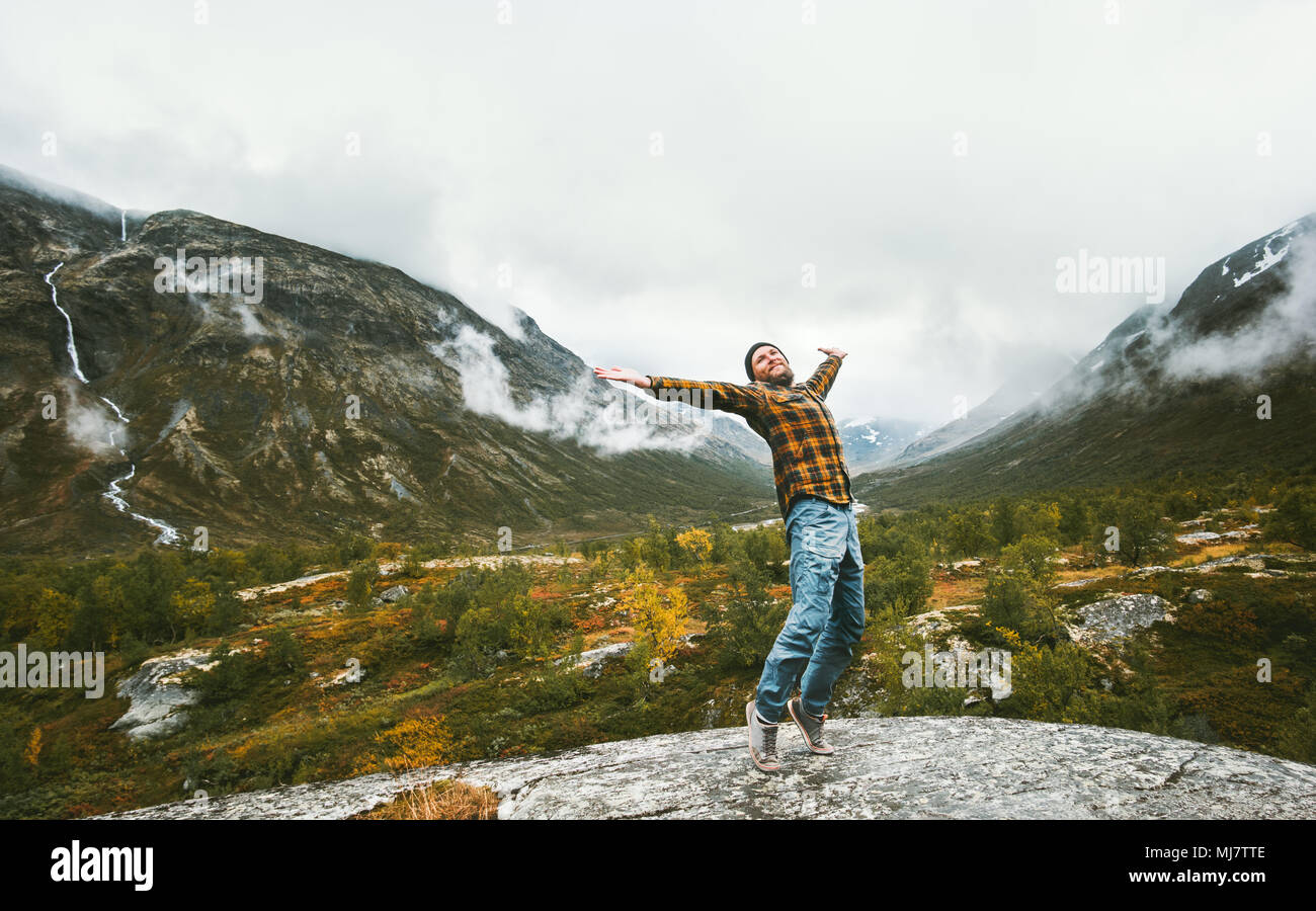 Happy man enjoying landscape view foggy forest mountains Travel adventure healthy lifestyle concept active vacations in Norway - Stock Image