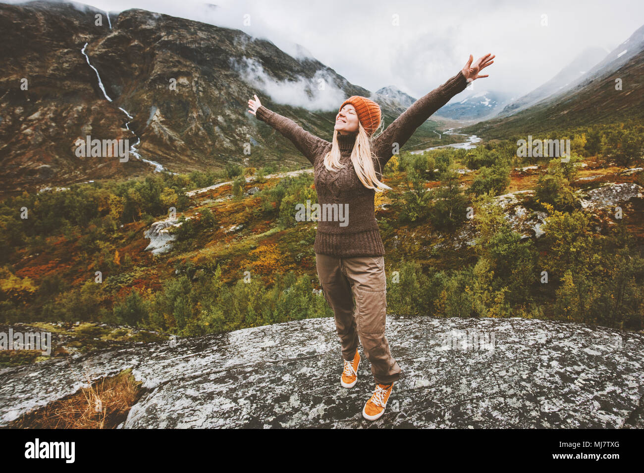 Happy woman traveler raised hands walking in forest mountains Travel adventure healthy lifestyle concept vacations - Stock Image