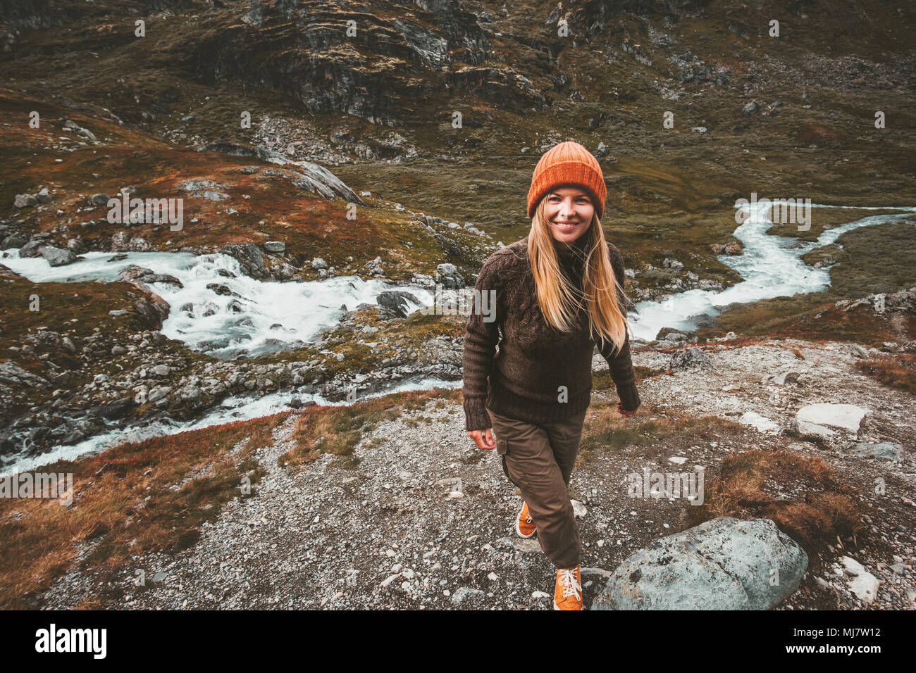 Happy young woman walking alone in scandinavian mountains Travel adventure lifestyle concept active vacations in Norway - Stock Image