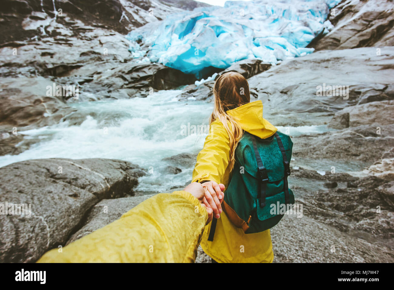 Couple travelers follow holding hands in  mountains glacier love and Travel lifestyle concept active adventure hiking vacations in Norway wild nature - Stock Image
