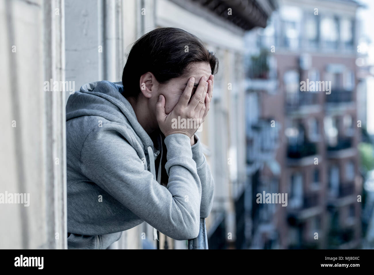 young Latin. sad and depressed woman standing on a balcony feeling over overwhelmed and suffering depression in mental health concept - Stock Image