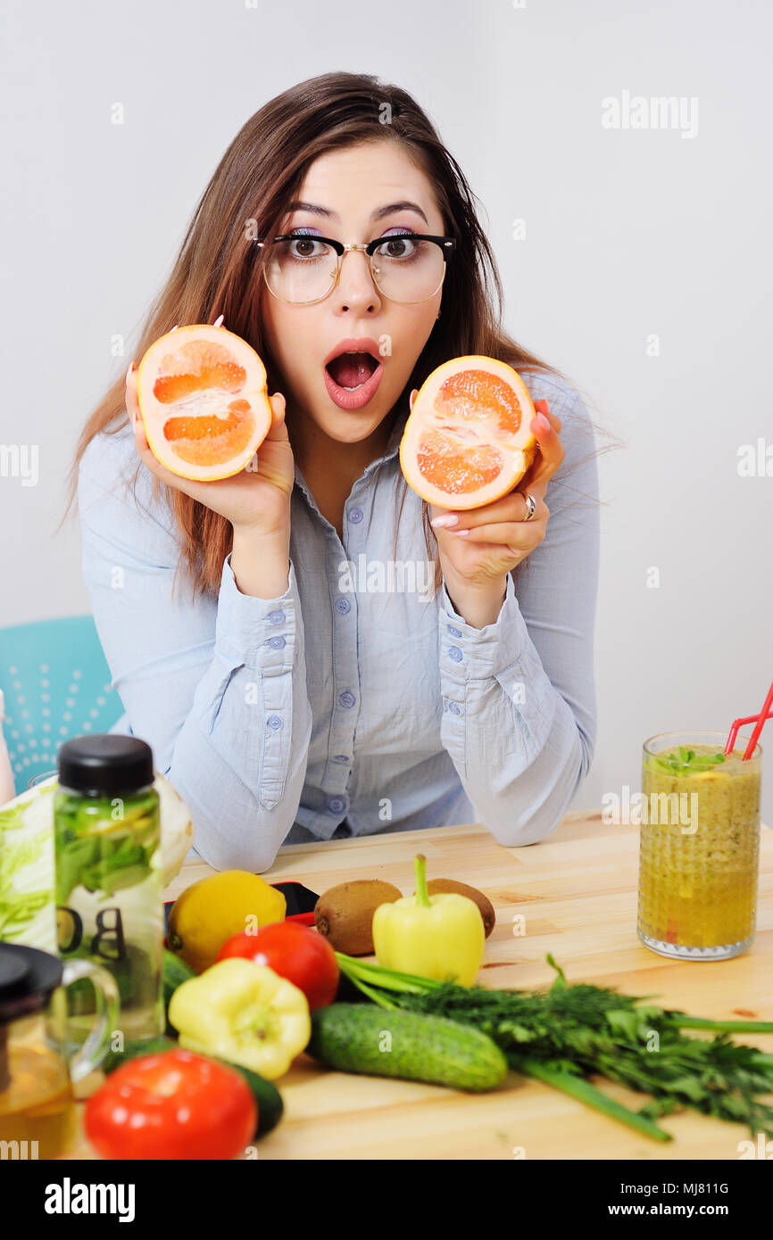 cute young girl with half a grapefruit in hands on a background table with vegetables.  - Stock Image