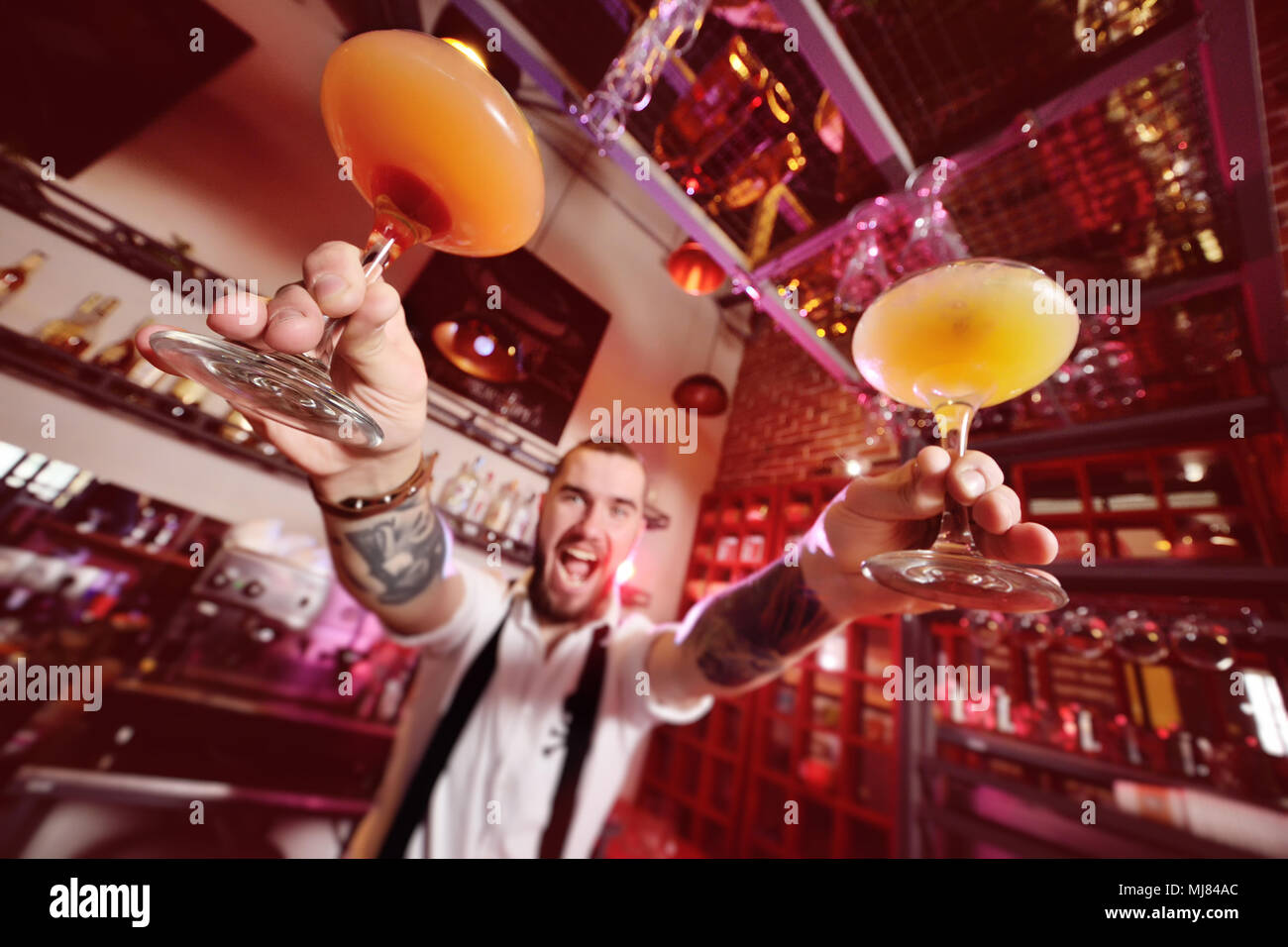 young bartender smiling and giving the client a cocktail of orange color - Stock Image