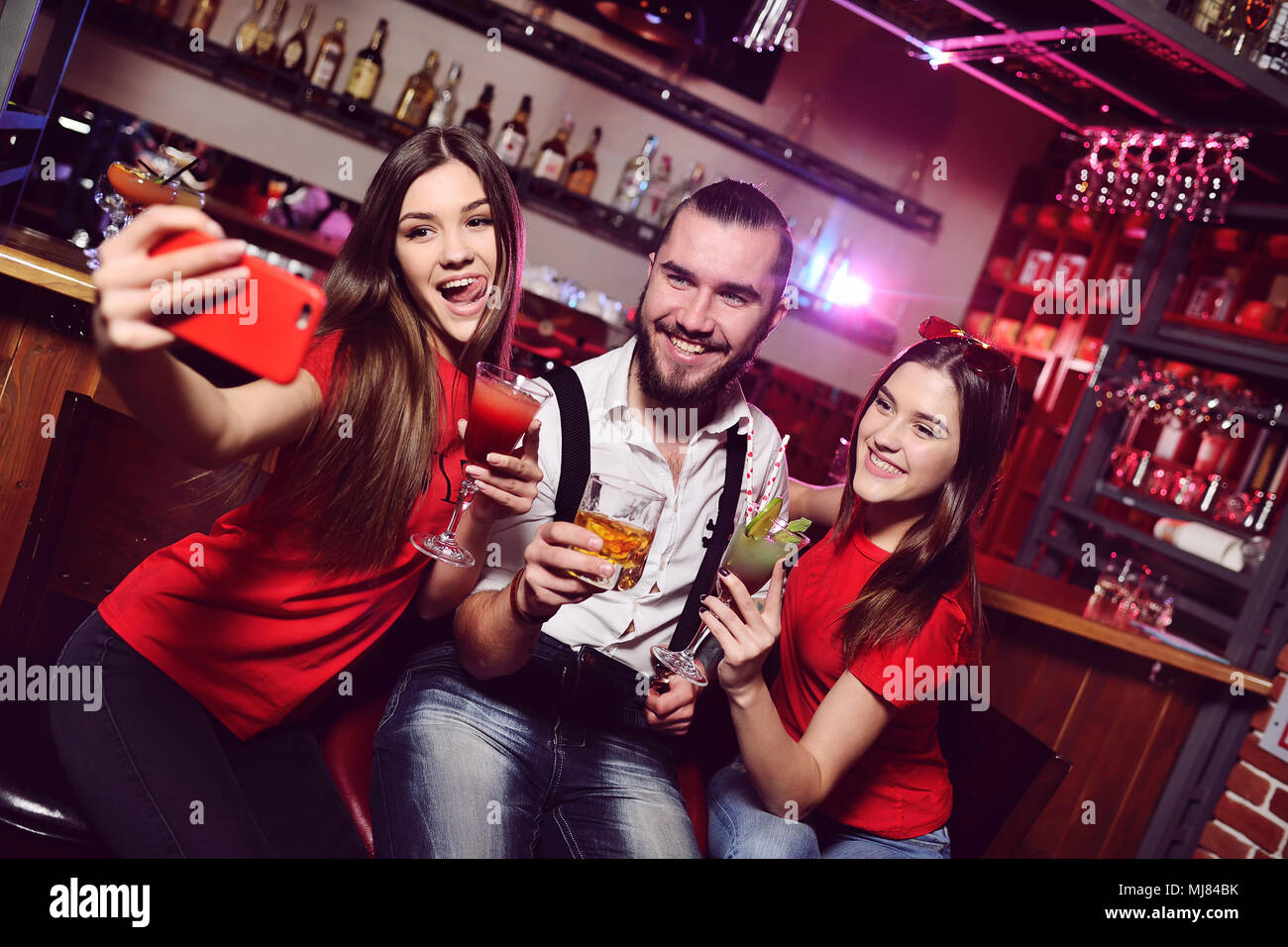 friends - two young attractive girls and a guy at a nightclub party make a photo of themselves on a mobile phone or smartphone - Stock Image