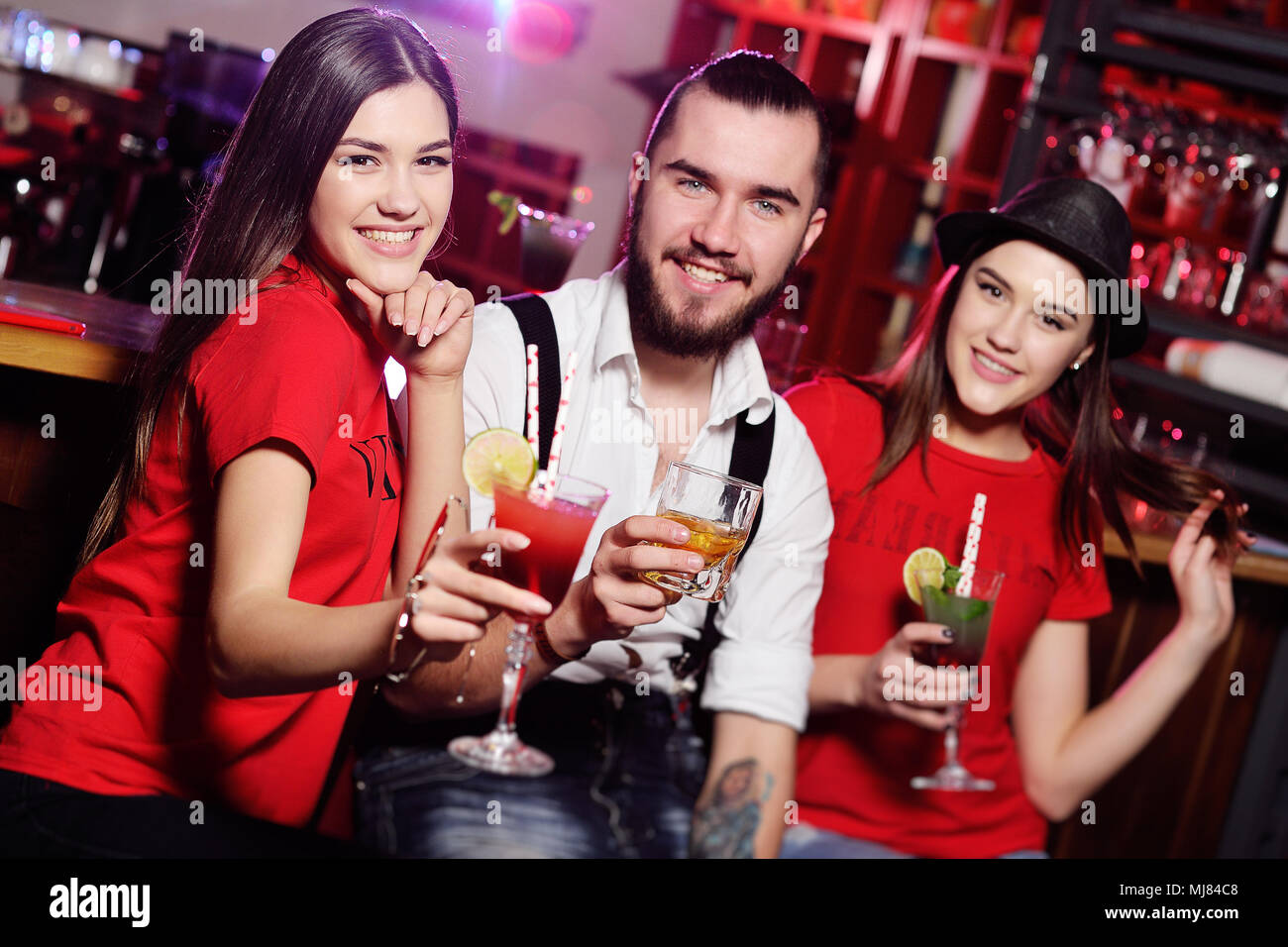 three friends - cute guy and two attractive young girls at a party holding cocktails in front of a bar smiling - Stock Image