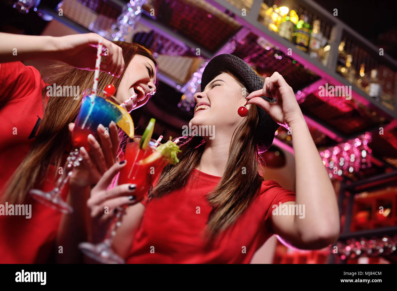 two attractive young friends at a party laugh with cocktails in the hands of a bar. - Stock Image