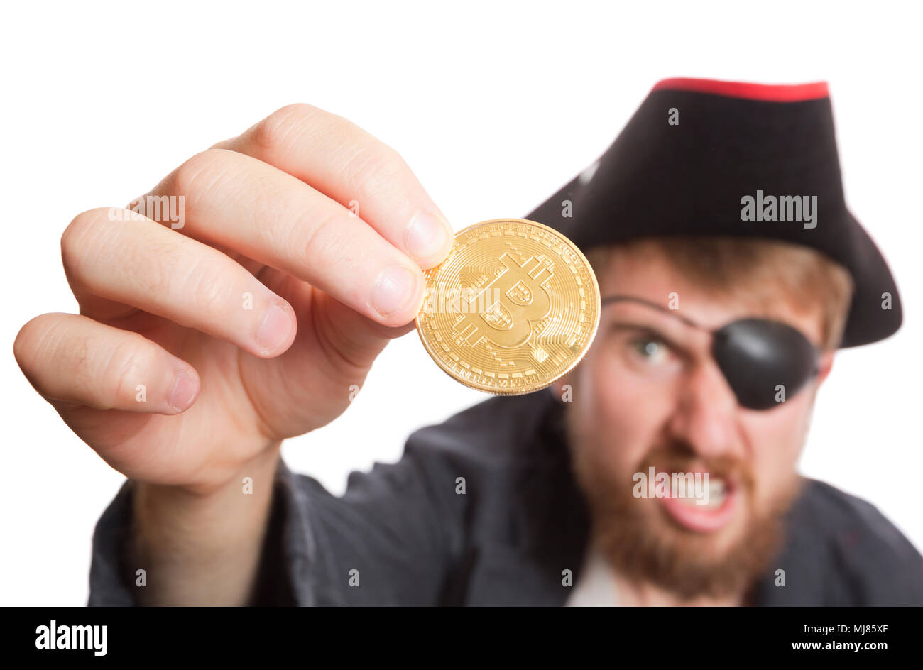 A pirate holding a bitcoin up and grimacing, banking concept. - Stock Image