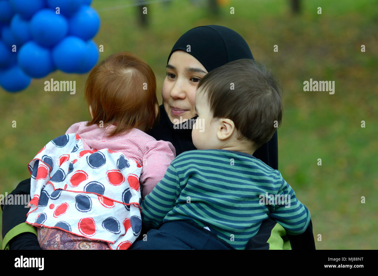 Muslim woman in hijabs carrying  baby on her arms. Celebration of Hidirellez (festival of arrival of spring).Kiev, Ukraine - Stock Image