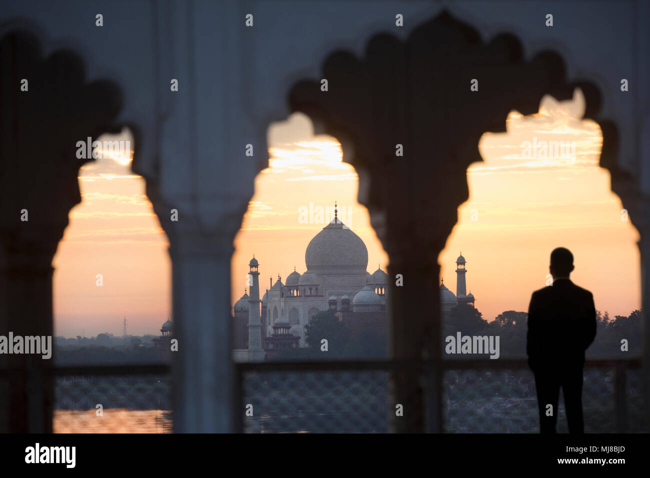 Rear view of man standing underneath scalloped arch on balcony at sunset, Taj Mahal palace and mausoleum in the distance. - Stock Image