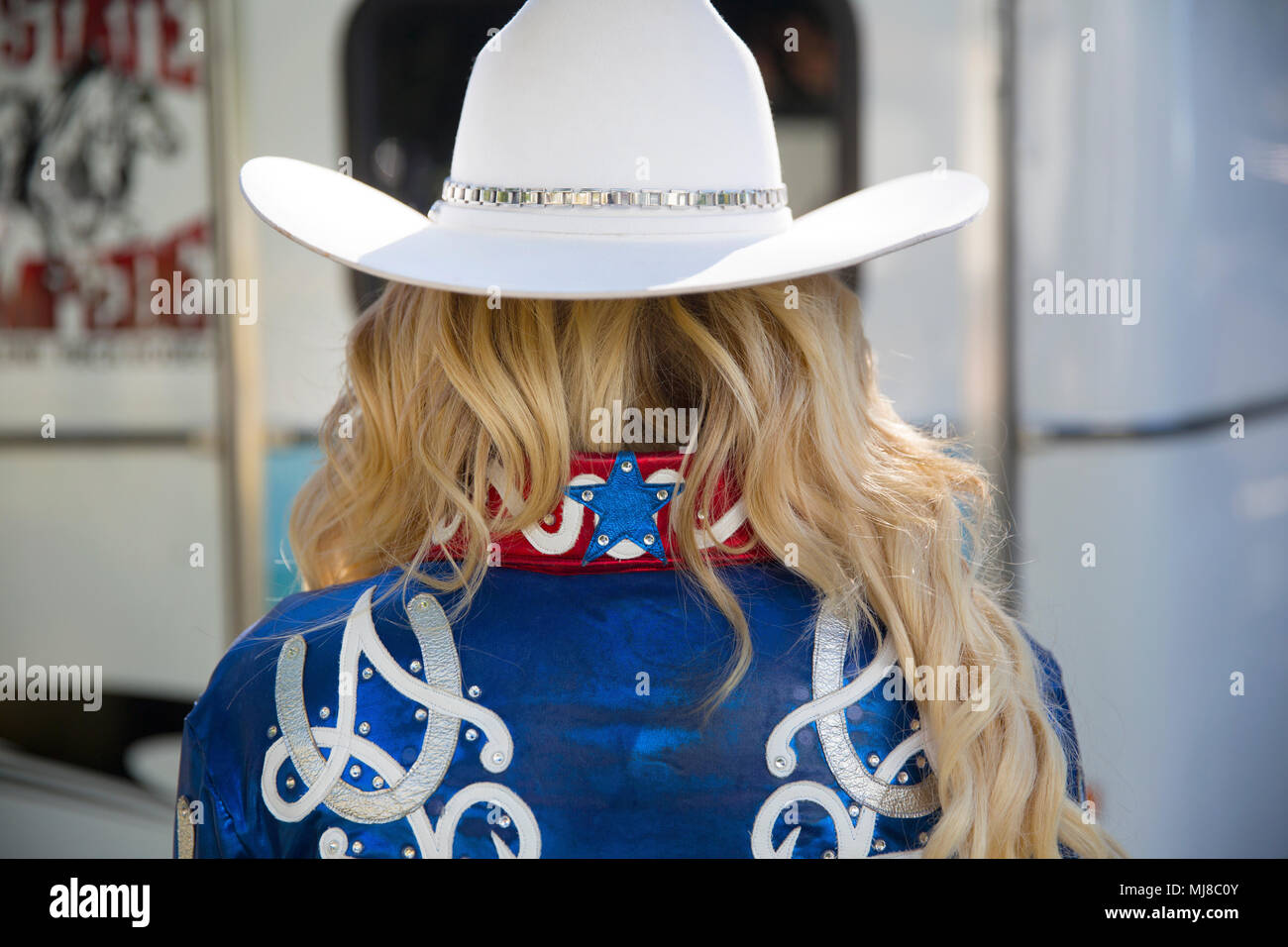 4e7f387d74eed Rear view of woman with long blond hair wearing white Stetson hat and shiny  blue jacket