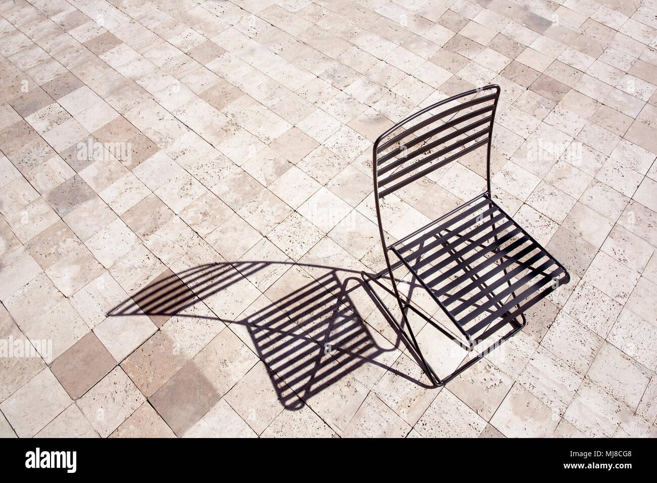 High Angle View Of Black Metal Folding Chair Casting Shadow Onto Brown  Paving.
