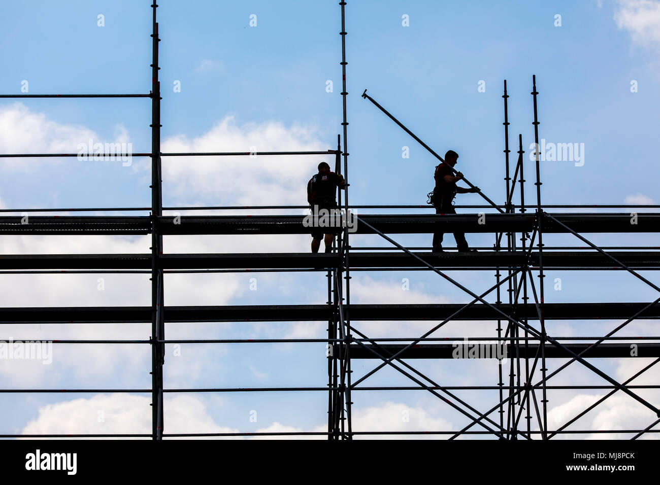 Scaffolding builder during the dismantling of a large, free-standing scaffolding, - Stock Image