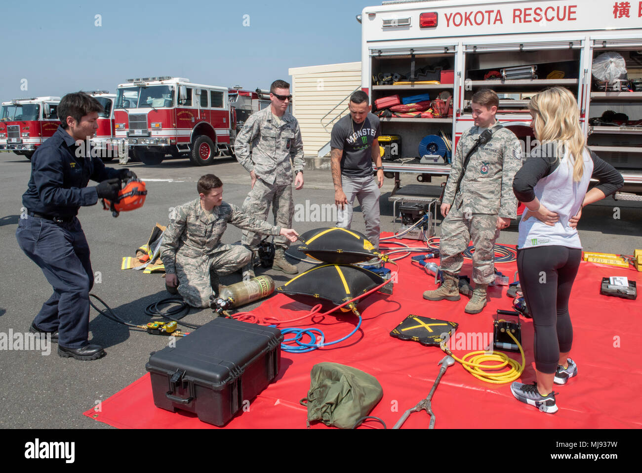 Firefighters from the 374th Civil Engineer Squadron demonstrate the usefulness of high-pressure bags to USO Spring Tour entertainers Max Holloway and Paige VanZant at Yokota Air Base, Japan, April 22, 2018. Each year the USO produces more than 50 entertainment tours, bringing hundreds of individual shows to hundreds of thousands of American service members around the world. (U.S. Air Force Photo by Airman 1st Class Matthew Gilmore) - Stock Image