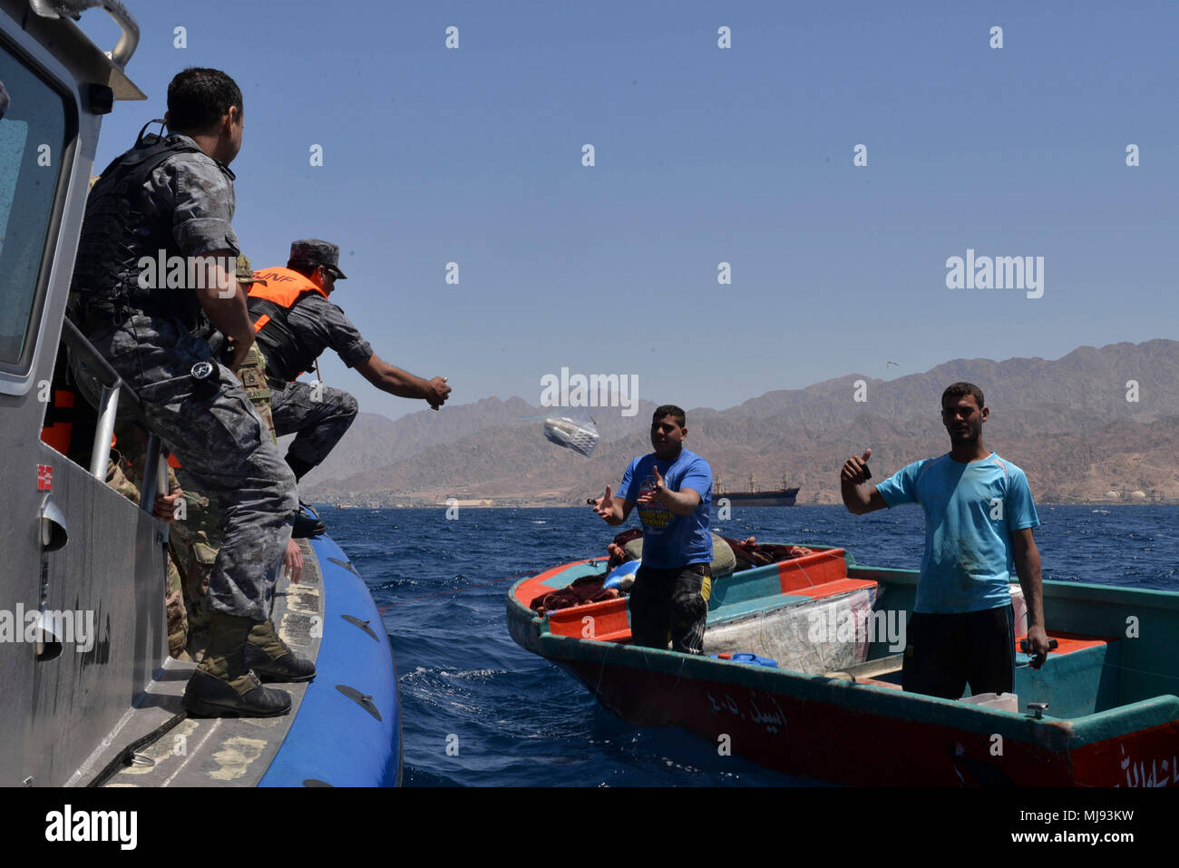 AQABA, Jordan (April 23, 2018) --  Members of the Royal Jordanian Navy Combat Boats Group toss a medical supply kit to local Jordanian fishermen in a civilian outreach event with U.S. Army Civil Affairs during exercise Eager Lion, April 23, 2018.  Eager Lion is a capstone training engagement that provides U.S. forces and the Jordan Armed Forces an opportunity to rehearse operating in a coalition environment and to pursue new ways to collectively address threats to regional security and improve overall maritime security.  (U.S. Navy photo by Mass Communication Specialist 1st Class Sandi Grimnes Stock Photo