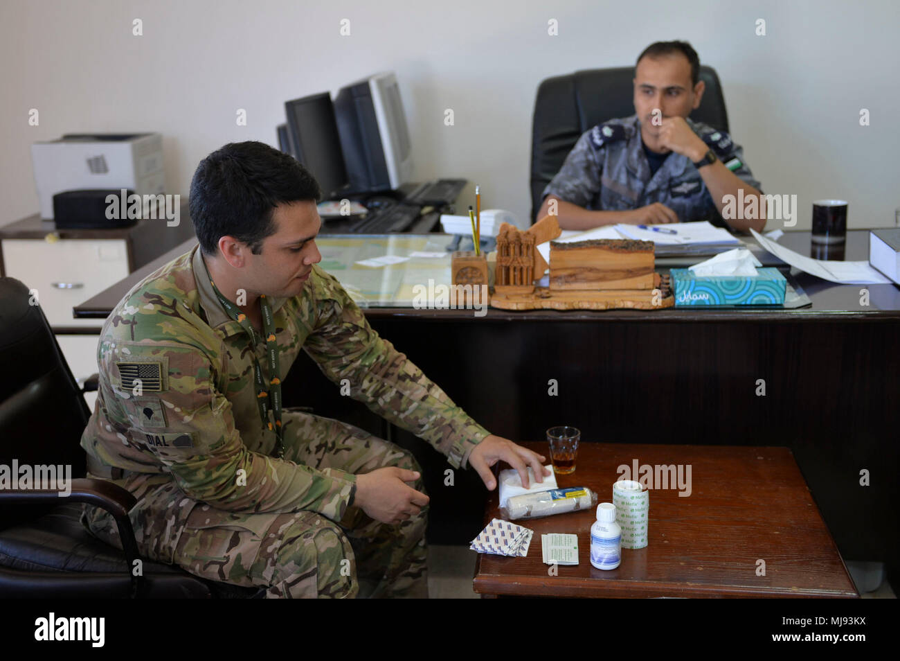 AQABA, Jordan (April 23, 2018) -- U.S. Army Spc. Caleb Dial with U.S. Army Civil Affairs, shows Lt. Cmdr. Mohannad AL-Namat, commanding officer, Royal Jordanian Navy Combat Boats Group,  medical supply kits prior to the outreach event with the local fishermen during exercise Eager Lion, April 23, 2018.  Eager Lion is a capstone training engagement that provides U.S. forces and the Jordan Armed Forces an opportunity to rehearse operating in a coalition environment and to pursue new ways to collectively address threats to regional security and improve overall maritime security.  (U.S. Navy photo Stock Photo