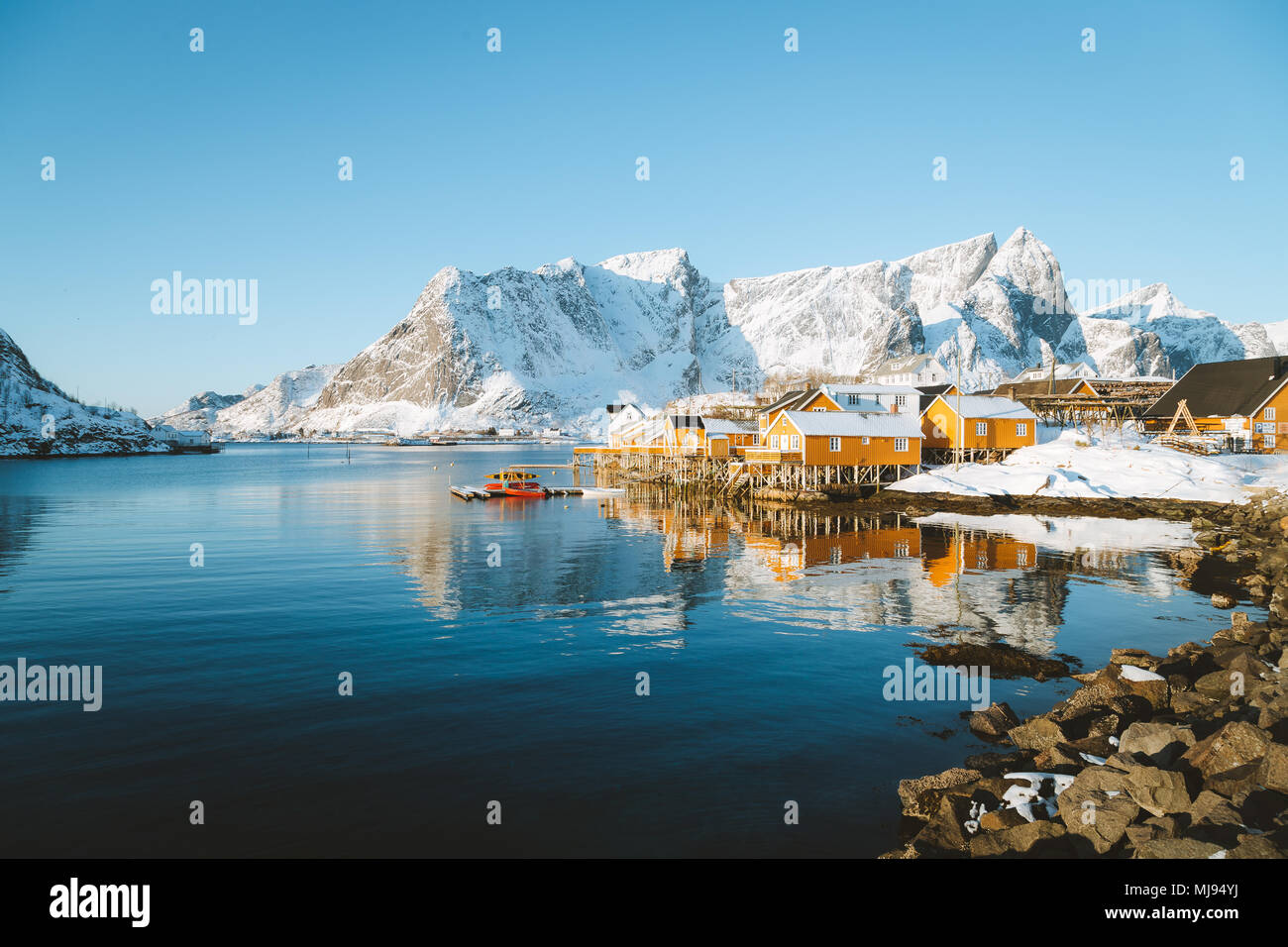 Beautiful Lofoten Islands archipelago winter scenery with traditional yellow fisherman Rorbuer cabins in the historic village of Sakrisoy, Norway - Stock Image