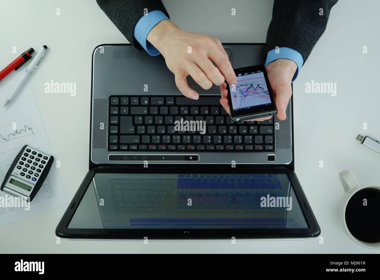 Working on a laptop and using smartphone - Stock Image
