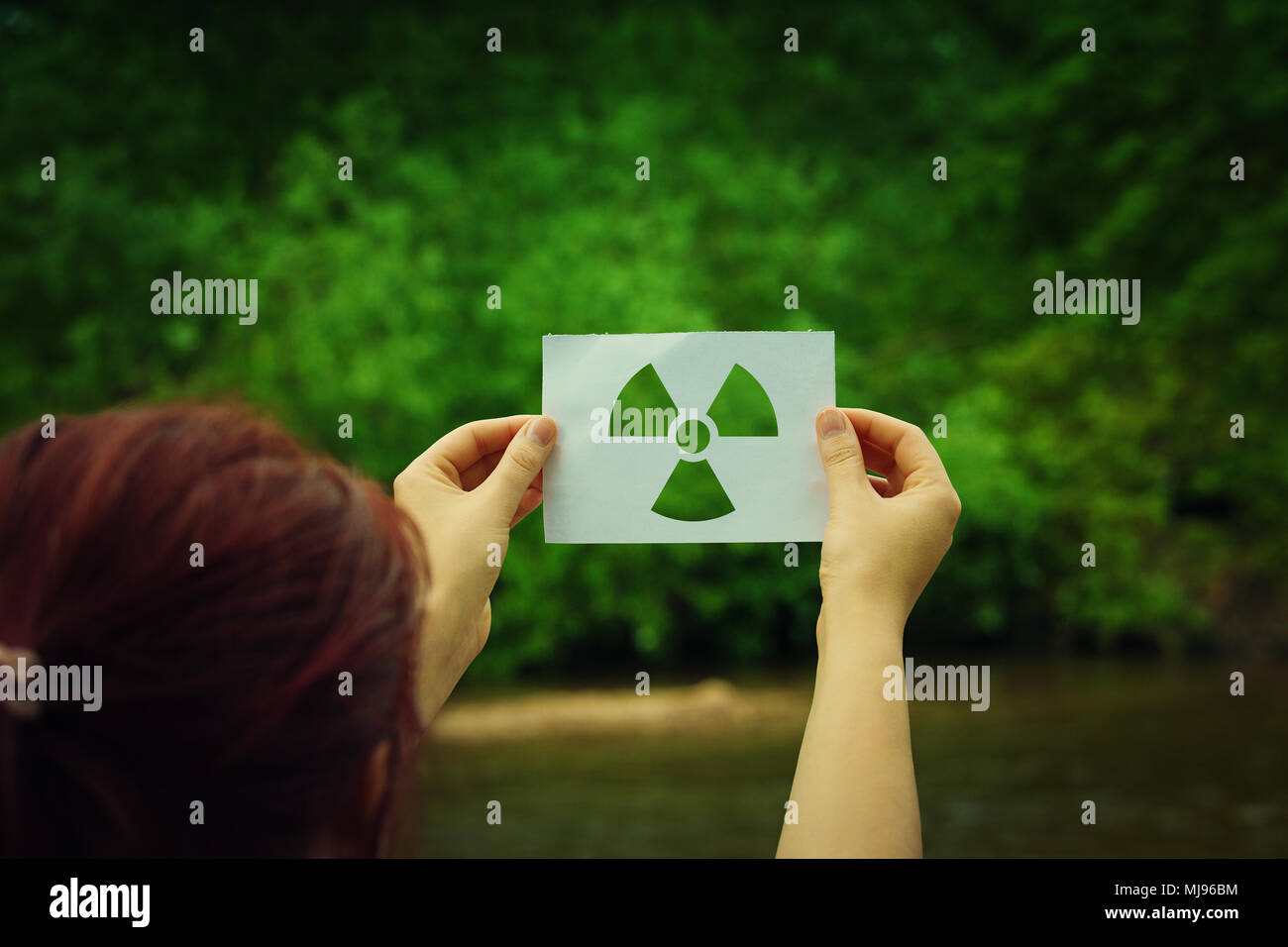 Woman holding a paper sheet with radiation symbol symbol over green forest background. Environmental problems concept, radioactive disaster as danger  Stock Photo