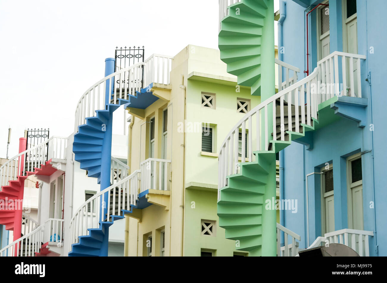 colorful spiral staircases at the back of traditional chinese shop houses in singapore city Stock Photo