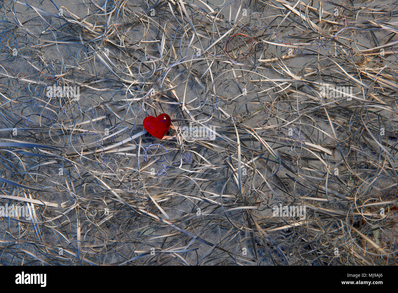 A red glass heart at the centre of a tangle of card offcuts on a background of slate. False colour has turned the white card metallic. - Stock Image
