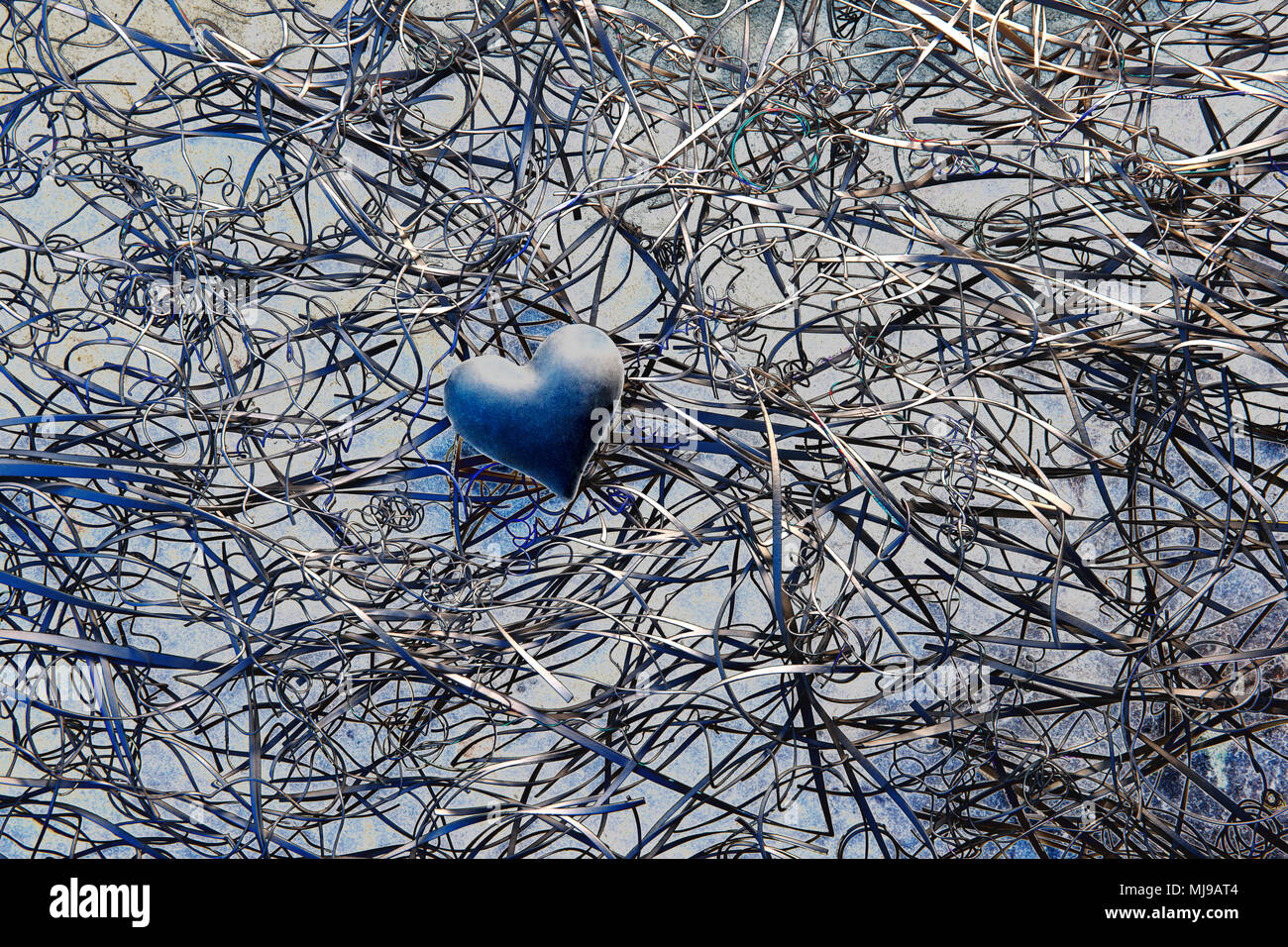 A dark blue heart at the centre of a tangle of card offcuts on a background of slate. - Stock Image