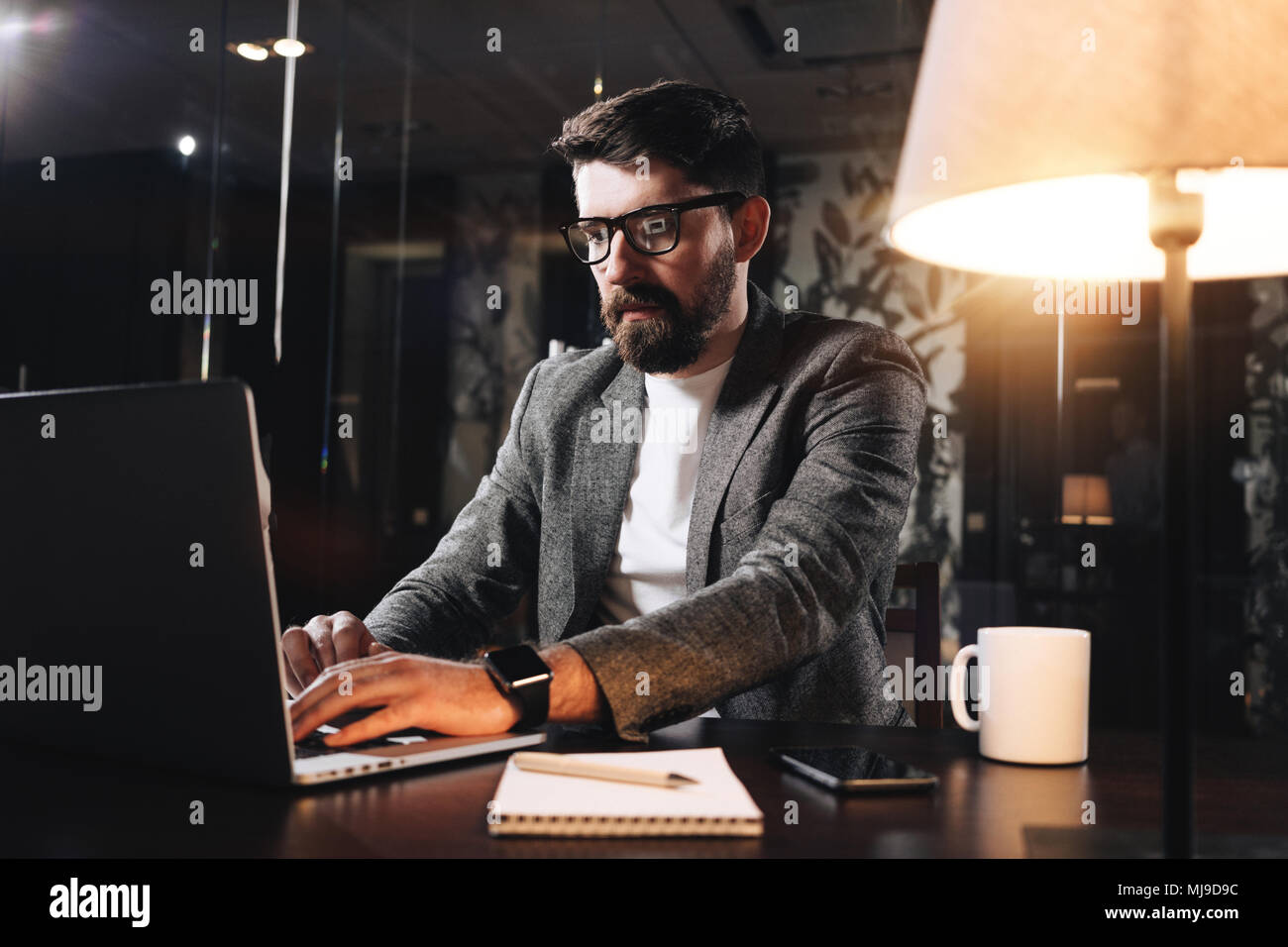 Bearded young businessman working on open space office at night. Man using modern notebook, typing text. Coworker working. Film effect - Stock Image