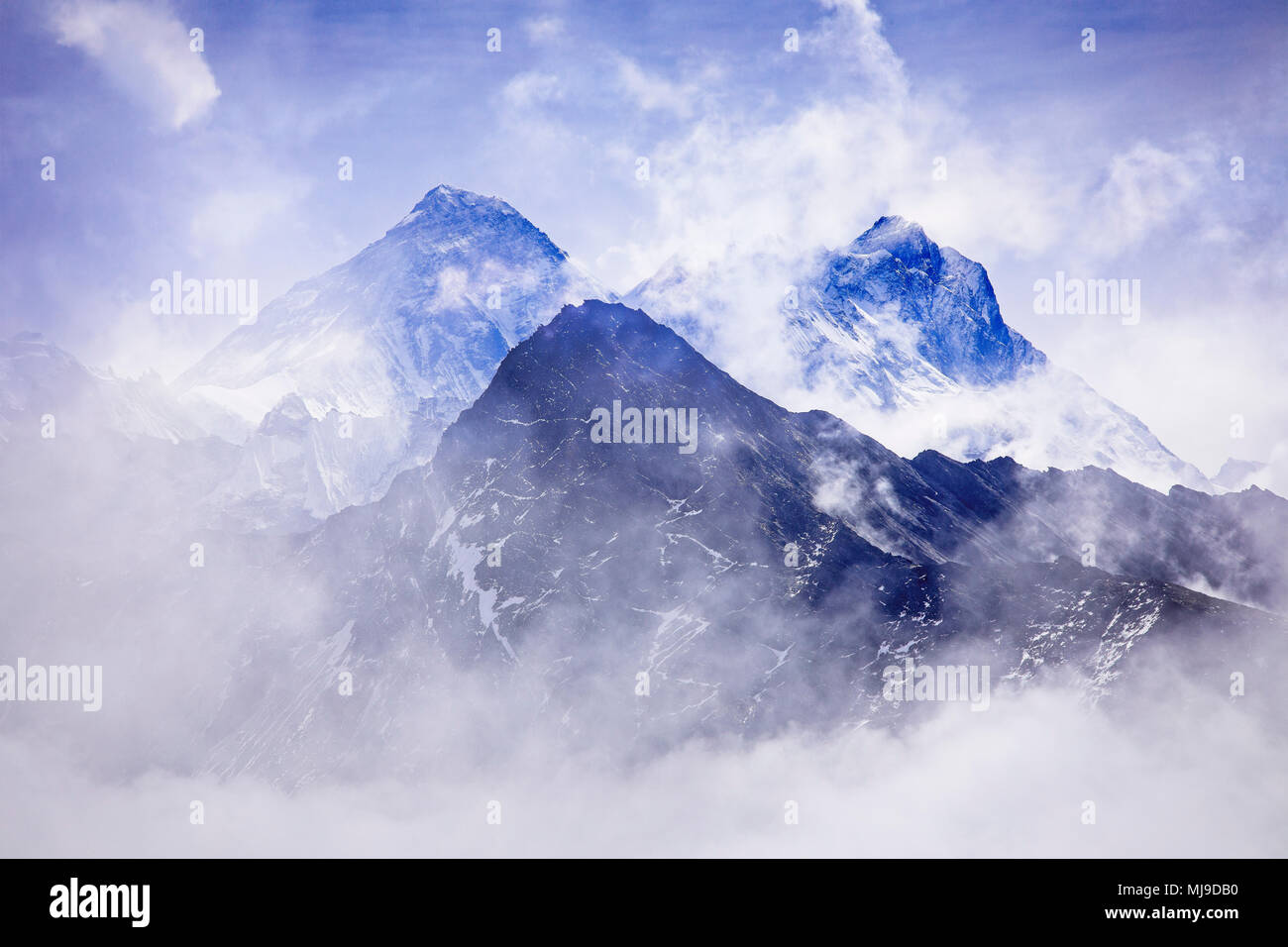 Mt. Everest and Nuptse through the clouds in Sagarmatha National Park, Nepal. - Stock Image