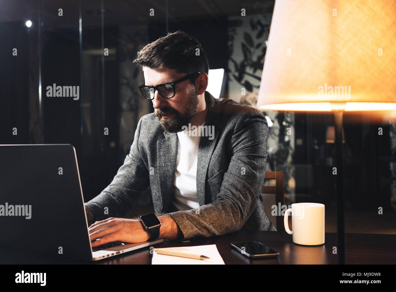 ef3acfa23 Young bearded businessman sitting at wooden table with lamp in loft office  at night. Project manager working process and typing text on contemporary n