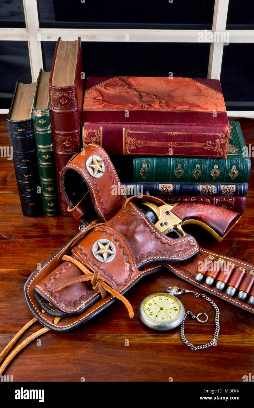 Old cowboy gun in holster with pocket watch and literature Stock