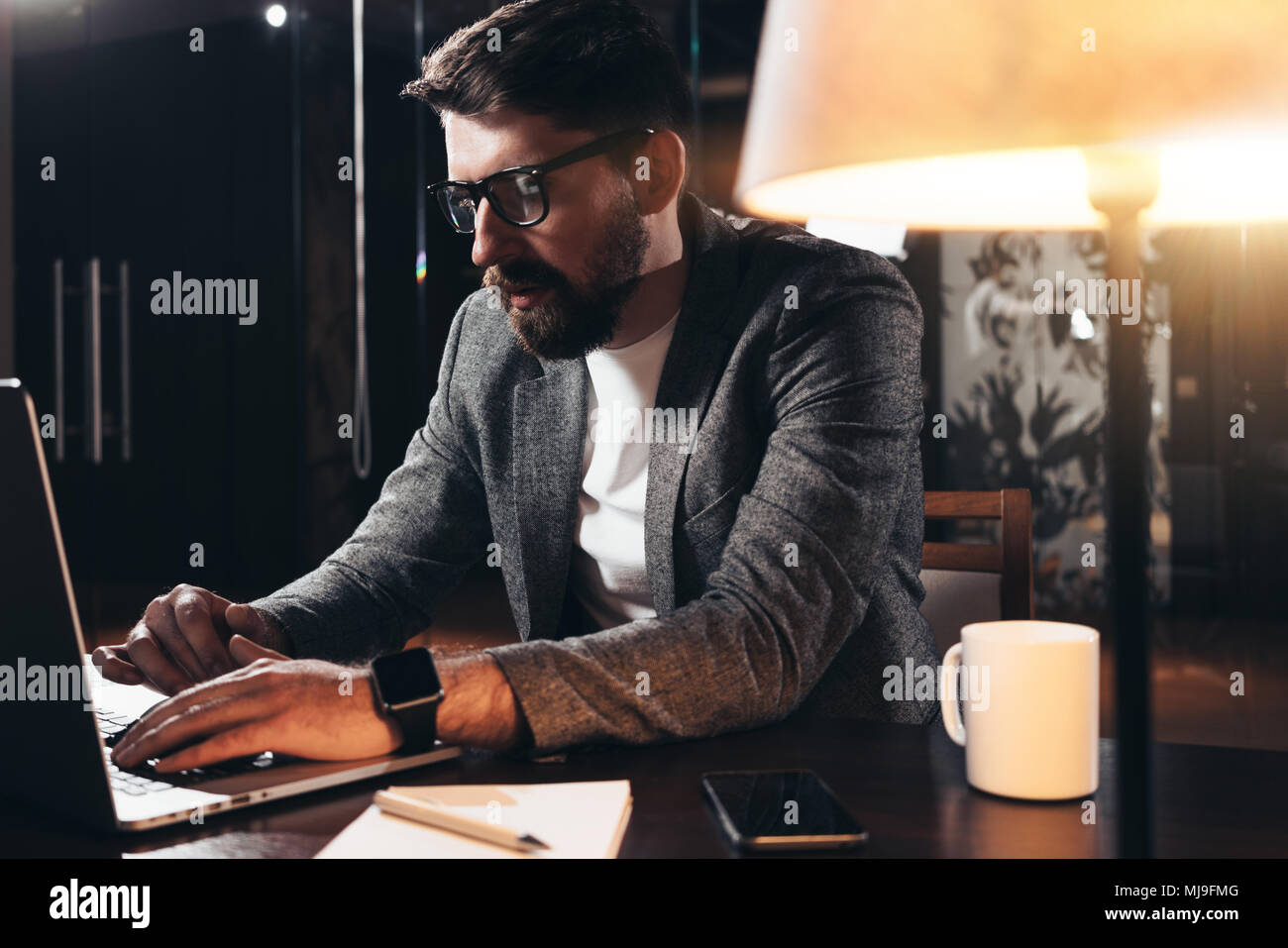 Bearded young businessman working in loft space at night. Coworker sits by the wooden table with lamp and office tools. Project manager using contempo - Stock Image