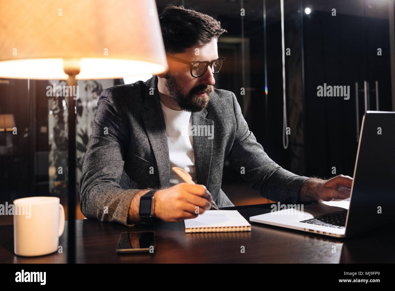 Bearded project manager hold pen in hand and using contemporary notebook. Young businessman working in loft office at night. Man making new startup - Stock Image