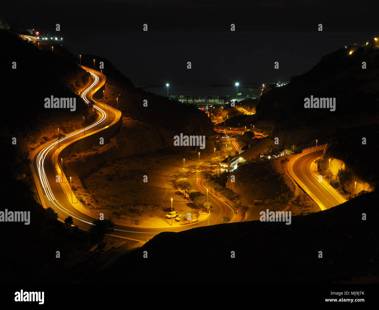Winding road lit up with street lights - Stock Image