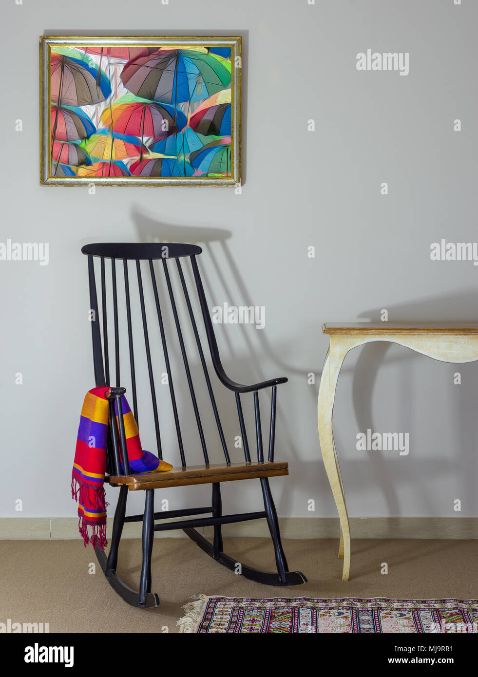 Classic rocking chair and off white vintage table on background of off white wall with hanged painting including clipping path for painting - Stock Image