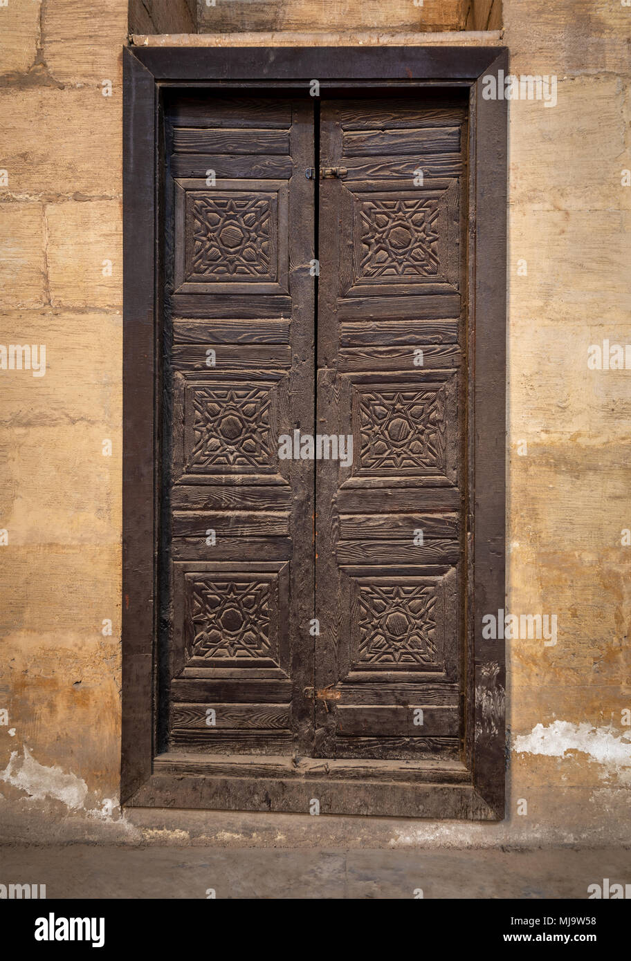 Wooden aged grunge door and stone bricks wall, Medieval Cairo, Egypt - Stock Image