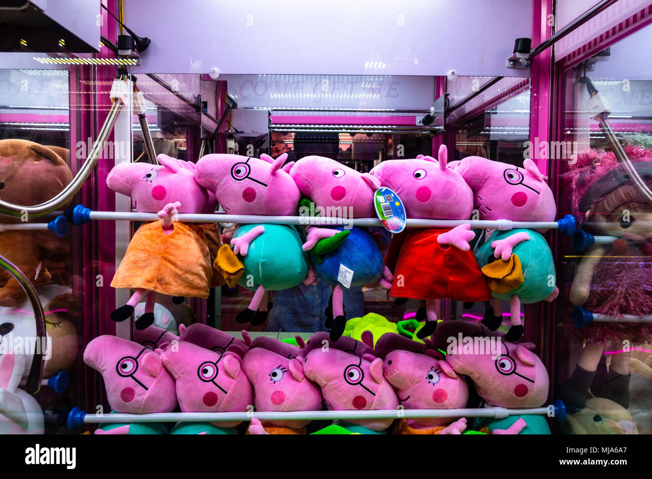 Peppa Pig plush dolls toys inside a claw machine - Stock Image
