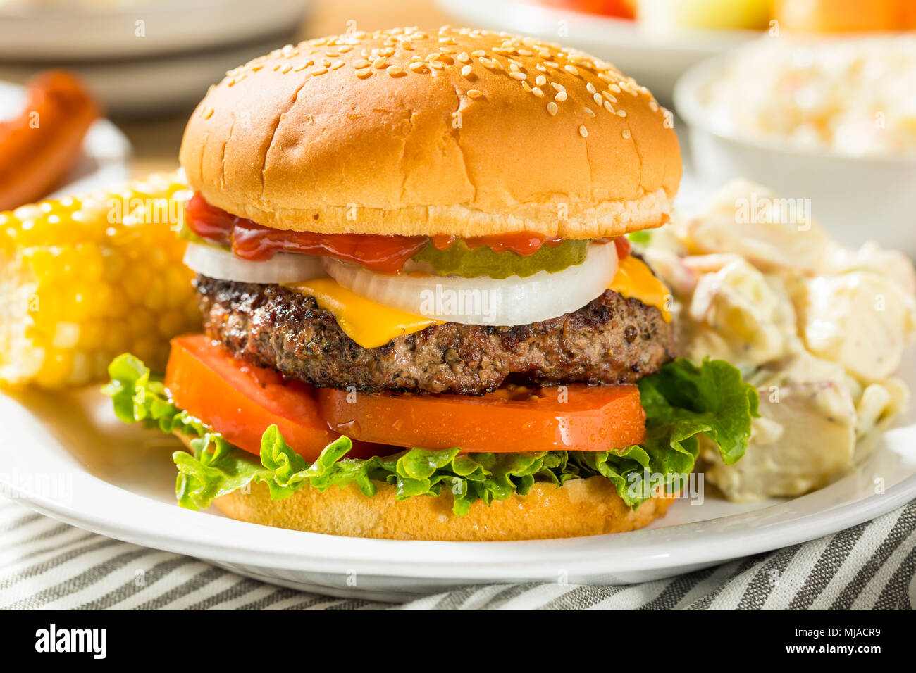 Memorial Day Backyard Babecue Meal with Hamburgers Hot dogs Salads and Chips - Stock Image