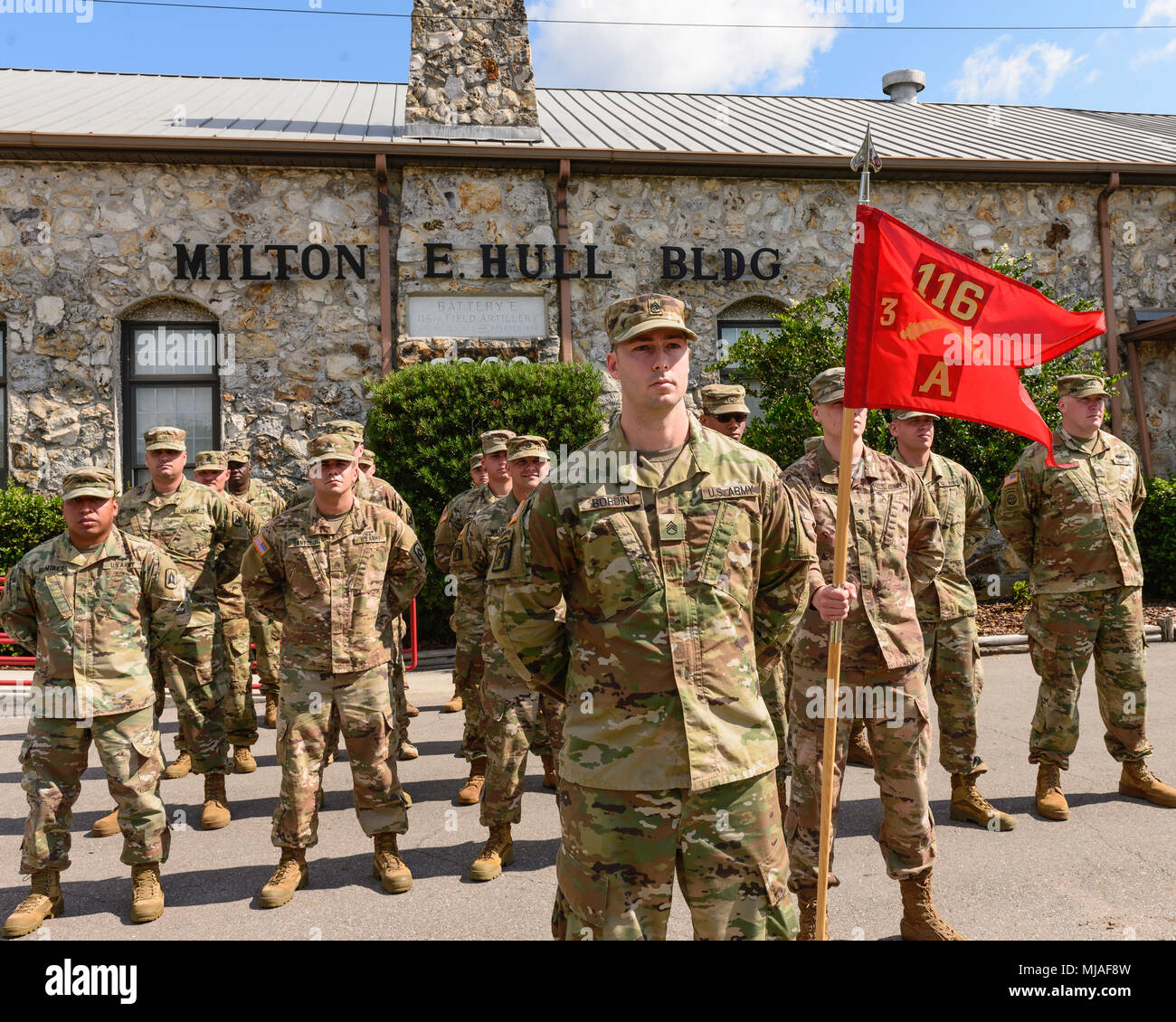 Approximately 30 Soldiers with the Florida National Guard's Battery A, 3rd Battalion, 116th Field Artillery Regiment stand in formation during their departure ceremony in front of the historic Milton E. Hull building at the Florida Strawberry Festival Fairground in Plant City. This building housed members of the Plant City-based FLNG unit from shortly after World War II until their current armory was constructed many decades later. - Stock Image