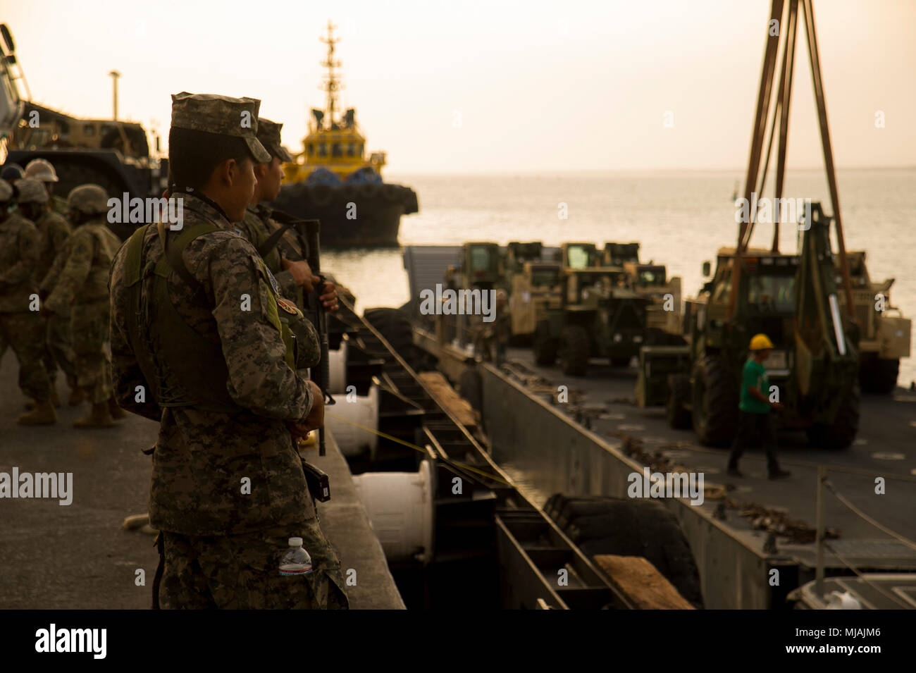 ACAJUTLA, El Salvador (April 22, 2018) Salvadorian marines look on during pier-side Lift On/ Lift Off operations of an Improved Navy Lighterage Causeway Ferry during Joint Logistics Over the Shore (JLOTS) 18. JLOTS 18 is part of U.S. Southern Command's exercise Beyond the Horizon, led by U.S. Army South, that helps to bolster regional and partner relations through humanitarian and civic assistance projects, medical readiness exercises, and exercise related construction projects taking place in El Salvador. (U.S. Navy photo by Mass Communication Specialist 2nd Class Kenneth Gardner/Released) - Stock Image