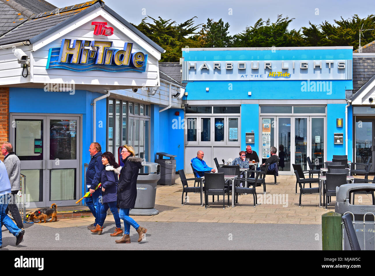 Holidaymakers Stroll Past The Hi Tide Inn U0026 Harbour Lights  Bar/entertainments Centre On The Seafront At The Seaside Resort Of  Porthcawl. South Wales.