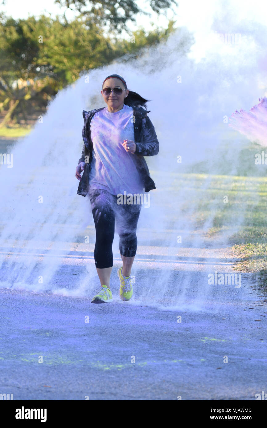 U.S. Air Force Tech. Sgt. Cecile Chatman, 81st Medical Support Squadron information systems NCO in charge, runs through purple powder during the Air Force Assistance Fund Color Run at Keesler Air Force Base, Mississippi, April 20, 2018. The AFAF raises funds for charitable affiliates that provide support to Air Force families in need. (U.S. Air Force photo by Kemberly Groue) - Stock Image