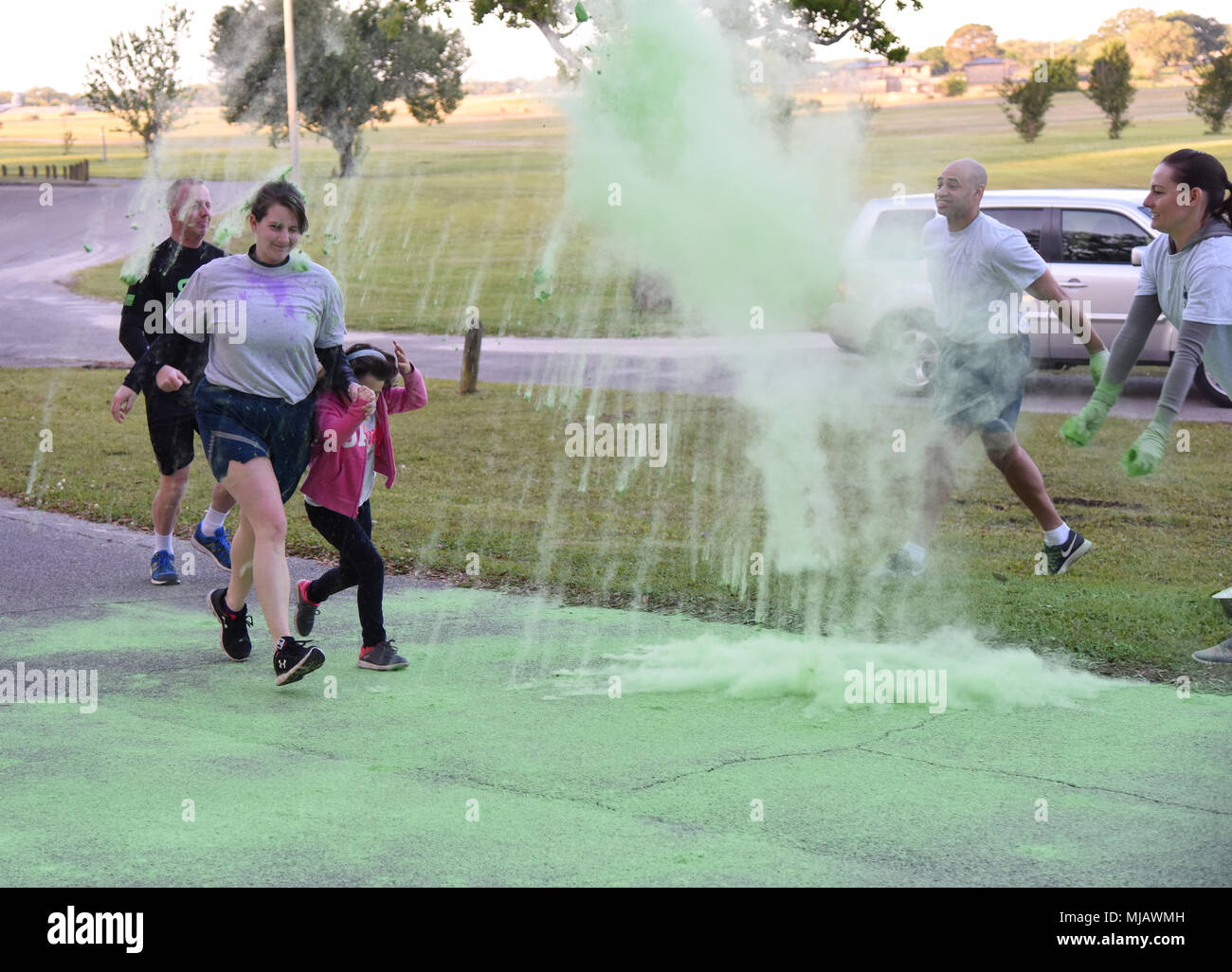 Keesler personnel run through green powder during the Air Force Assistance Fund Color Run at Keesler Air Force Base, Mississippi, April 20, 2018. The AFAF raises funds for charitable affiliates that provide support to Air Force families in need. (U.S. Air Force photo by Kemberly Groue) - Stock Image