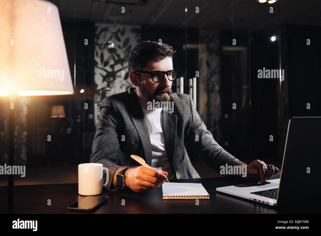 Young bearded project manager using modern laptop in loft office at night. Businessman working process. Film effect - Stock Image