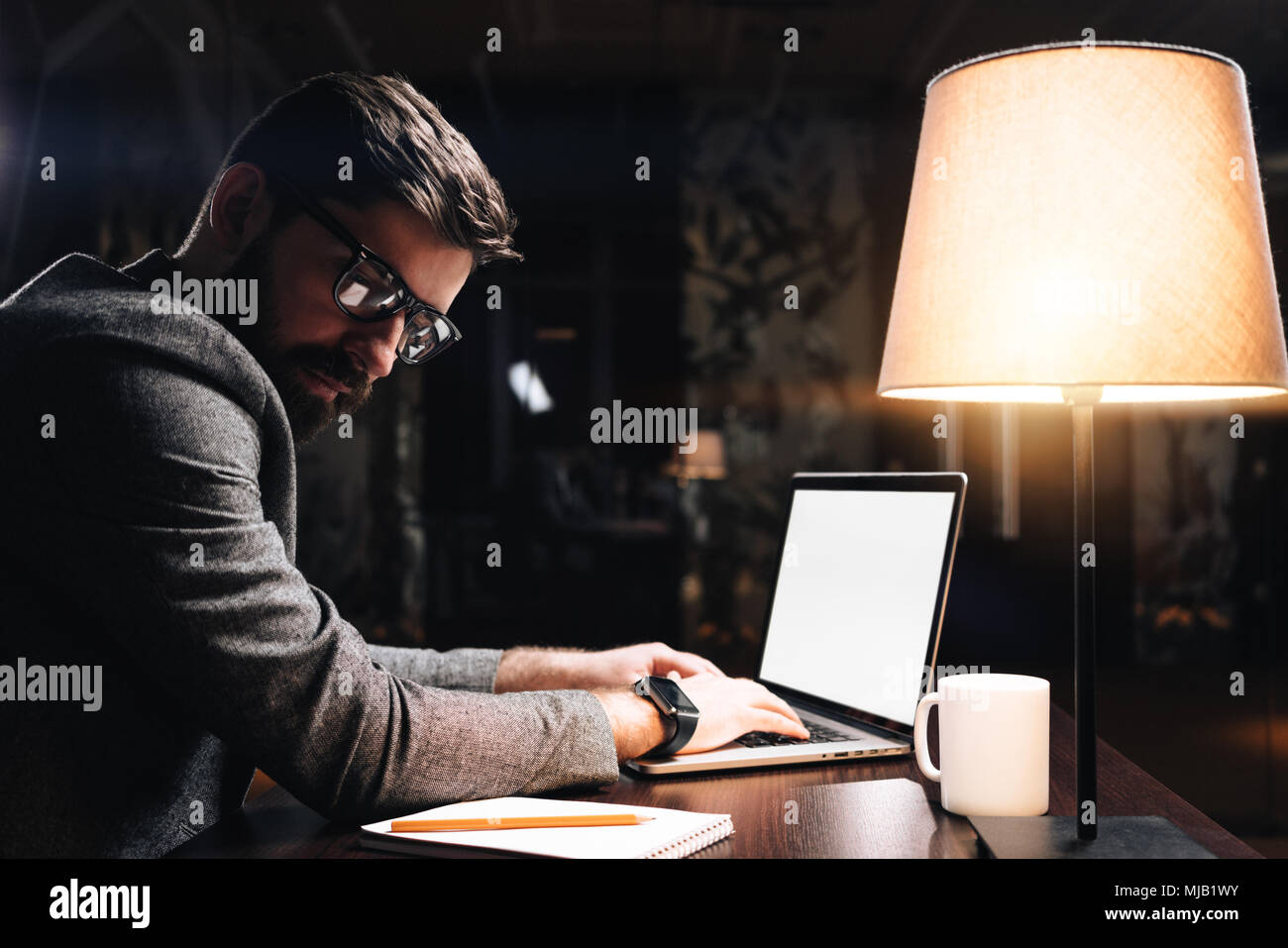 Bearded young coworker wearing glasses typing text on contemporary laptop in modern loft office at night. Business man sits by the wooden table with l - Stock Image