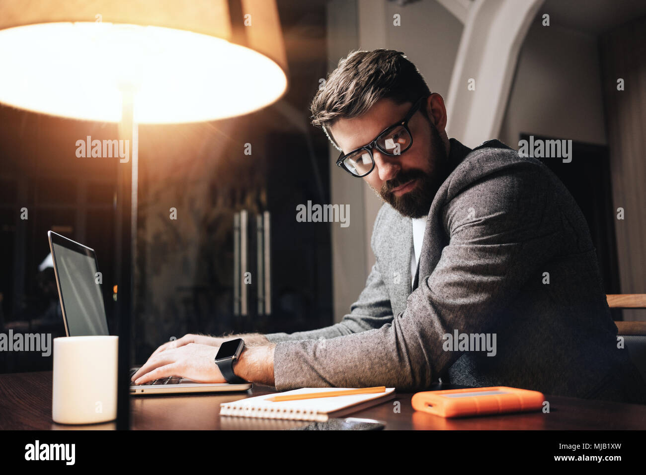 Bearded businessman in eye glasses working by the contemporary laptop at night coworker studio. Young project manager typing text on notebook. Film ef - Stock Image