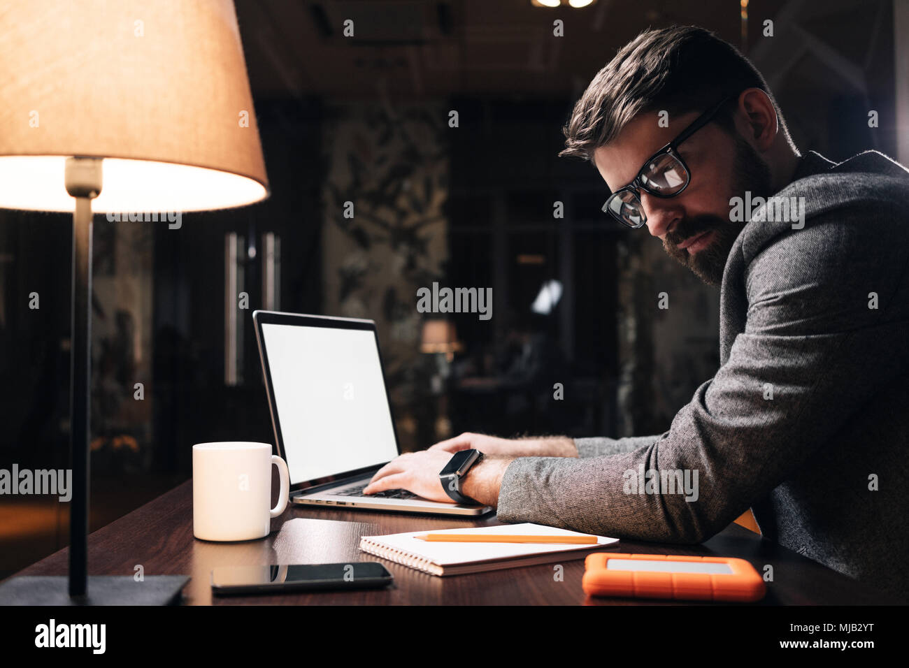 Young project manager typing text on laptop at night office. Bearded business man working on new startup in loft space. Coworker concept. Flare effect - Stock Image